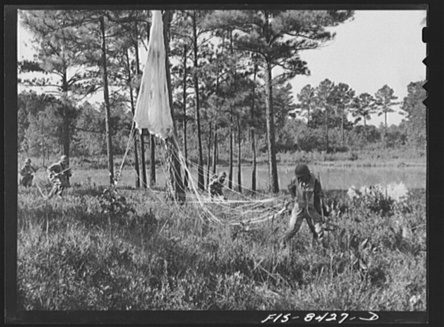 Fort Bragg, North Carolina. Parachutist advancing through the woods after landing in a military demonstration