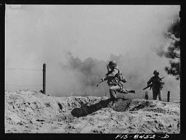 Fort Bragg, North Carolina. Parachutists leaping into a trench in a military demonstration