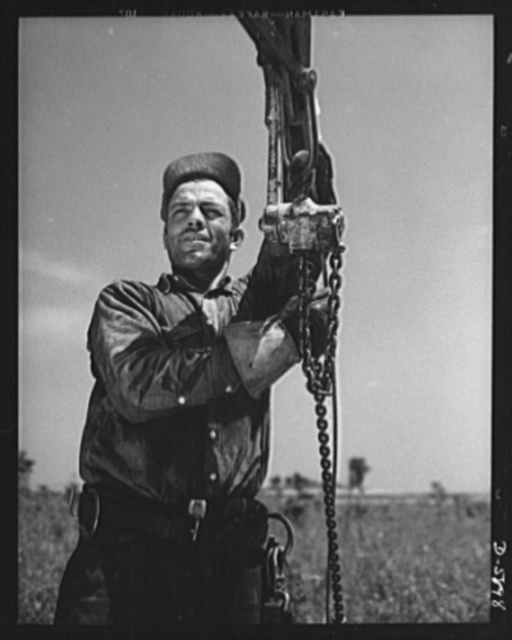 """Fort Knox. Electric power line construction. The electrical industry of America relies largely on the """"broadback"""" or lineman, to bring its power to the places where it is needed. This man is working on the construction of a transmission line to Fort Knox, Kentucky, where American soldiers are training for the battles of democracy"""