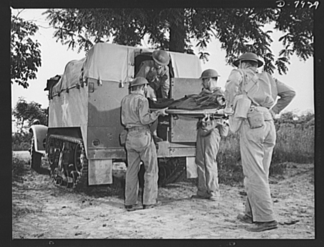 """Fort Knox. Halftrac crews. Lifting a """"wounded"""" tank crew member into a halftrac ambulance at Fort Knox, Kentucky. The Fort Knox school for men of the armored service is teaching many American soldiers how to use mechanized striking equipment to best advantage. Its graduates are now on many of our far-flung battle lines, ready to meet the Axis on more than even terms"""