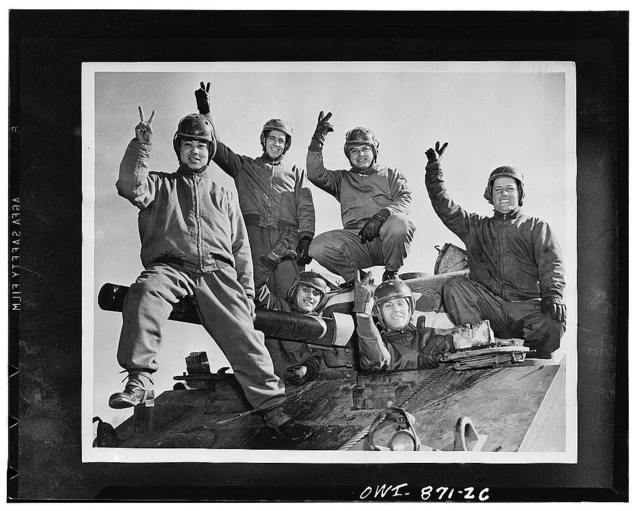 Fort Knox, Kentucky. Armoraiders symbolizing six nations atop a powerful medium tank: Private Richard Do Yee of China; Corporal Austin Chamberlain of England; Sergeant John Evans of Russia; Private Alexander Scourles, a revengeful Greek, and driver Henri de Charmont of the Fighting French. The tankman on the right is Private Johnny Smith of the United States