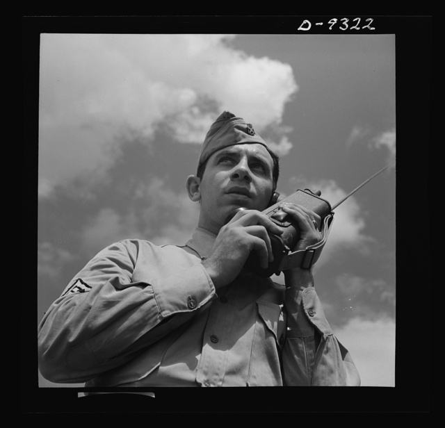 "Fort Myer, Virginia. A sergeant at Fort Myer, Virginia demonstrates a ""walkie-talkie"" in the field. This is the latest and most compact two-way radio in use by the Army. The unit is complete, containing batteries, mechanism, and aerial which telescopes into the case when not in use for this instrument"