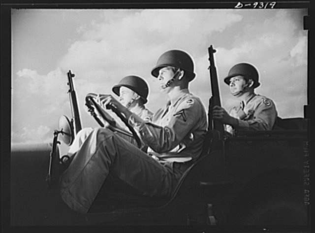 Fort Myer, Virginia. Alert and ready for action are these rough-riding, hardboiled members of a jeep crew at Fort Myer, Virginia. Properly equipped with new type helmet and Garand rifles, these soldiers of Uncle Sam's armoured forces typify the ruggedness and determination of the American fighting men