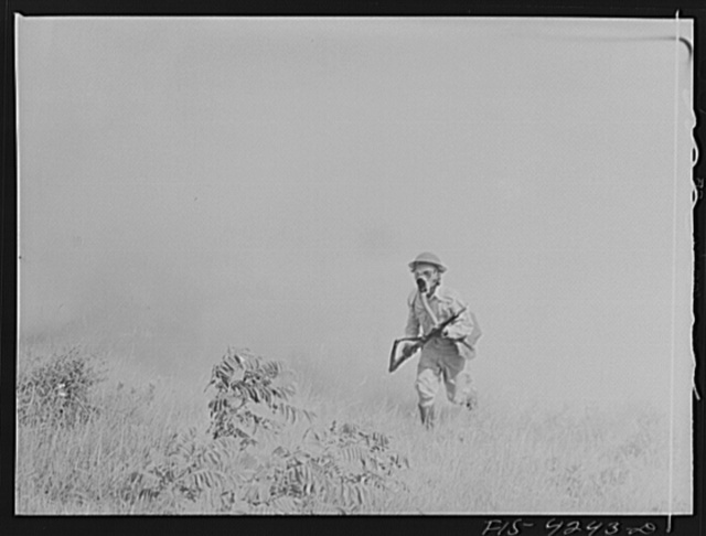 Fort Riley, Kansas. A soldier of a rifle platoon of a calvalry unit advancing through a smokescreen during a sham battle