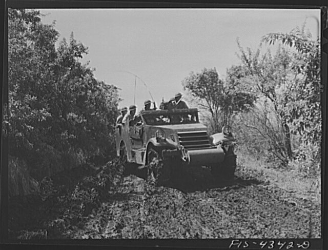 Fort Riley, Kansas. Scout car maneuvering along a muddy road during a sham battle