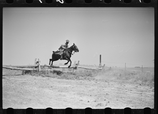Fort Riley, Kansas. Soldiers of a cavalry machine gun platoon going over an obstacle during a field problem