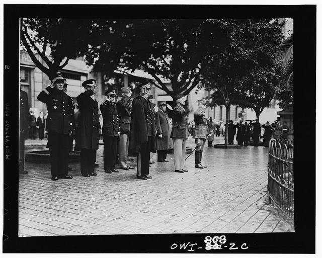 French and American officers saluting during flag raising ceremonies somewhere in North Africa. First row, right to left: the French General Boiseau; American Major General Lloyd R. Fredendhall; third party unidentified