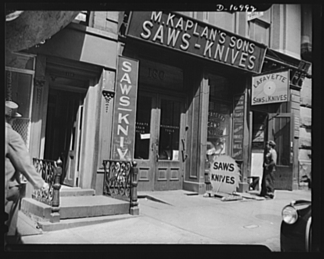 Front of establishment. Behind this modest storefront in downtown New York City, workmen are turning out hundreds of small parts for machine guns, aircraft, marine engines and other tools of war--another example of how small manufacturers can share in war work through subcontracting
