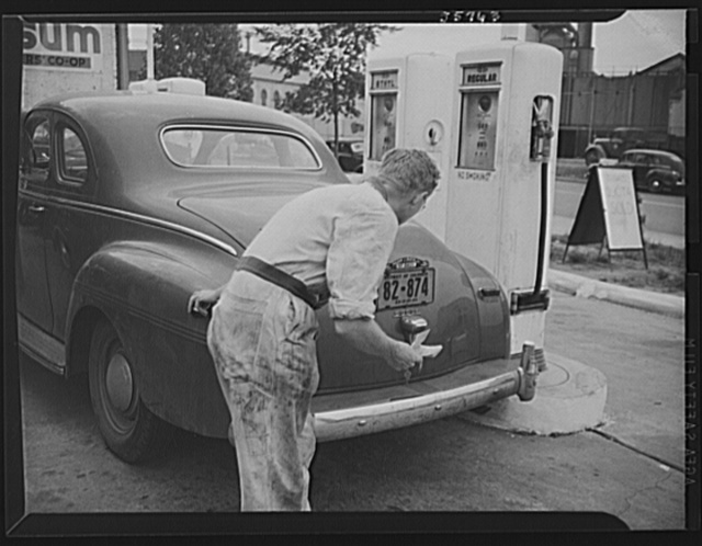 "Gas station attendant checking ration coupons against license plate of Washington, D.C. Dodge automobile. Sign on sidewalk reads ""Today's quota sold"""
