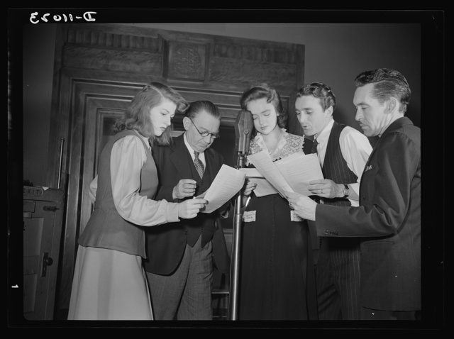 """Gathered around the microphone during rehearsal are (left to right) Virginia Moore, Colonel Charles Ferris, Doris McWhirt, John Flynn, and Robert Pollard. They make transcriptions four times a month for the series of radio shows, """"You Can't Do Business With Hitler,"""" which is written and produced by the radio section of the Office of War Information (OWI)"""