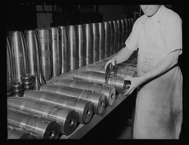 Gauging shells for big guns. New, shiny shells for the Army's 155 mm guns being gauged during production at a large eastern arsenal