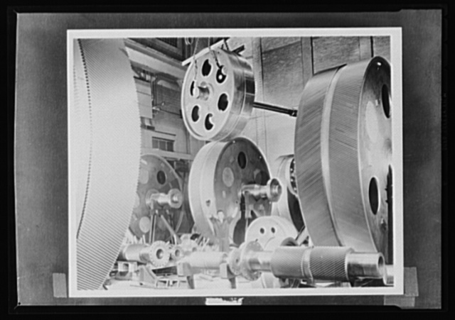 Gears to grind the Axis. Giant gears to guide America's fleets around the sees to victory. A workman, dwarfed by the towering wheels, directs the moving of a high speed gear blank to a hooking machine. The surge of the mightiest surf won't faze these titans, whose job it is to speed the day when the Axis will be blasted to the bottom of the ocean