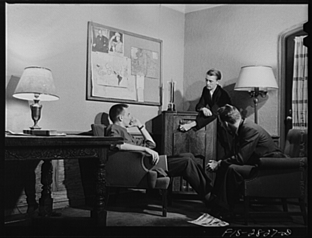 George Breckenridge, left, forestry student, from Chicago, Illinois, Michael Deane (at radio), general agriculture, from Buenos Aires, Argentina, and Gene Bopp, poultry husbandry, from Fergus Fall, Minnesota listening to latest news reports in the lounge of the men's dormitory at Iowa State College, Ames, Iowa