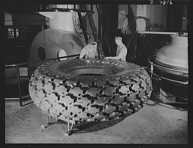 Giant tire manufacturer. Final inspection of the world's largest tire, the 36.00-40 earth mover, used in the construction of airports and new army camps. This huge tire stands nine and a half feet high, with tube and flap, weighs 3,646 pounds and carries 55,000 pounds. The giant mold in which it is vulcanized weighs 300,000 pounds and stands two and a half stories high when the cover is open. The top section of the mold which is raised and lowered to admit the tire, weighs sixteen tons. Large bullet- sealing gasoline and oil tanks are also being cured in this mold