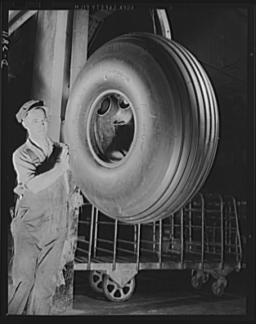 "Giant tire manufacturer. This bomber tire has just been removed from a mold and is on its way to final inspection, where it will be thoroughly checked before becoming a part of Uncle Sam's fighting forces. Airplane tire production is going forward twenty- four hours a day, seven days a week in this large Eastern plant in an all-out effort to ""Keep 'em flying"""
