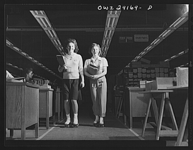 "Girls on wheels expedite aircraft production. Roller skates. Literally helping to speed the war effort, Dolores Richardson and Geneva Carpenter are """"expeditors"" at Douglas Aircraft in El Segundo, California, where they deliver inter-departmental messages on roller skates"
