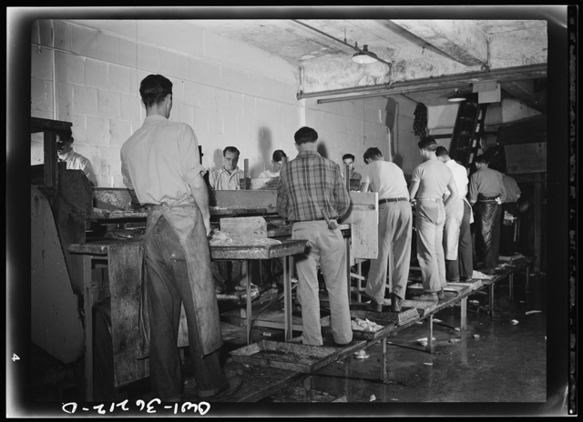 Gloucester, Massachusetts. Men on the filleting line in a fish packing plant