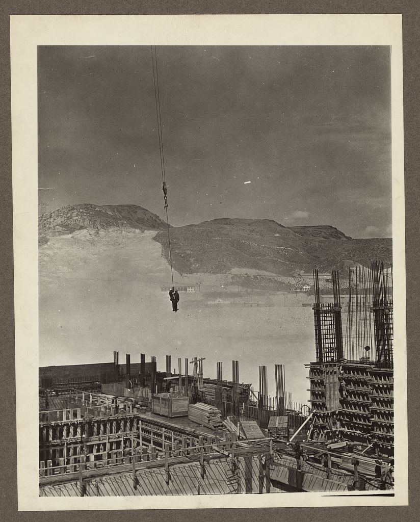 Grand Coulee Dam, Columbia Basin Reclamation Project, Wash. Two riggers on a hook on their way to work at the powerhouse on the right