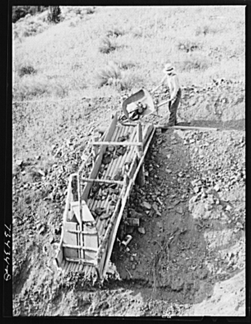 Grant County, Oregon. Miner dumping chrome ore into chute