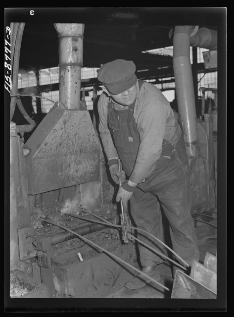 Great Falls, Montana. Anaconda Wire and Cable Company. Workmen putting unfinished rod into rolls of a finishing mill; from the wire bar to the finished rod, the processes of rolling are repeated so that the rod gets smaller and smaller until it is reduced to the desired size