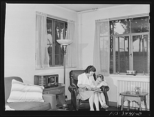 Greenbelt, Maryland. Federal housing project. Mrs. Leslie Atkins reading to her daughter Ann in the living room of her home. It is the corner house of a row of flat-roofed houses. All living rooms have cross ventilation