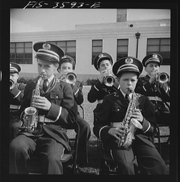 Greenbelt, Maryland. High school band in green uniforms giving a band concert on Memorial Day. Membership in the band is competitive, on the basis of talent. The band bought secondhand instruments and reconditioned them. It had made itself completely self-sufficient financially by giving benefit performances