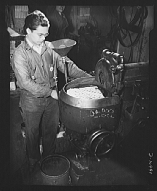 Grinding aircraft parts (one with inverted lamp shade). Tiny parts for aircraft are here being surface ground by a small machine shop in New York City whose peacetime products are industrial saws and knives. The same skill and machinery needed to produce saws and knives is thus being turned to the job of winning the war
