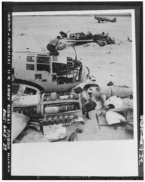Ground crews of the Allied air forces dismantle a wrecked Heinkel III on a landing field between Daba and Fuka in Egypt