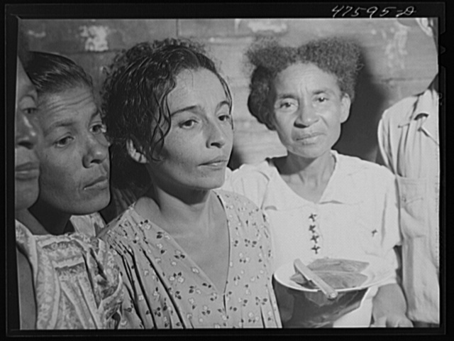 "Guanica, Puerto Rico (vicinity). At a Three Kings' eve party in the home of a farm laborer's family. The woman is serving ""pastellas,"" a tamale-like dish made with plantain"