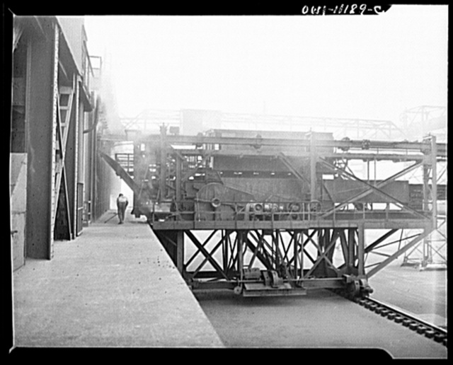 Hanna furnaces of the Great Lakes Steel Corporation. Detroit, Michigan. Coke oven pusher. A long square pusher is inserted through the entire section of the coke oven, thus pushing the coke out to the other side into the freight car. This coke oven is a modern by-product oven. All the gases and vapors liberated from the coal in the cooking processes are recovered. The coal is heated from fifteen to twenty hours in a temperature of about 1700 degrees F. The gases and vapors released by the coal are condensed for the recovery of such by-products as tar, benzol, and gas. At the end of the coking period, the incandescent coke mass is pushed into the quenching car