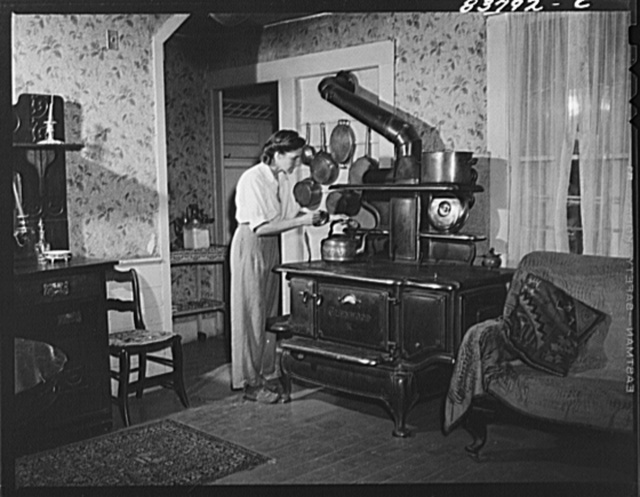 Hartford, Connecticut (vicinity). Mrs. Komorosky in her living room. Stove is for heat in winter, Russian style!
