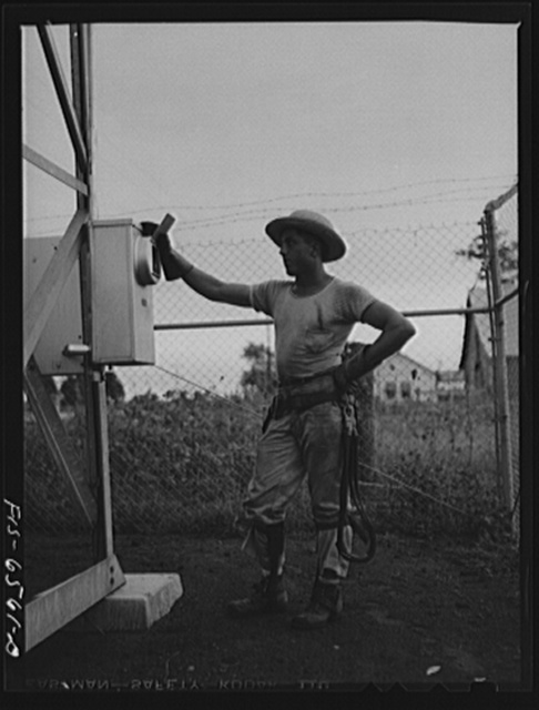 Hayti, Missouri. U.S. Rural Electrification Administration (REA) lineman inspecting a meter at a substation