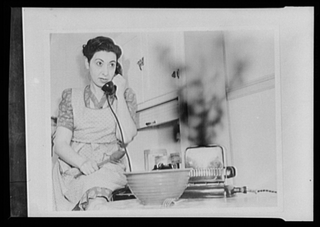 """Hitler's helpmates. Mabel Wattwaster is helping to win the war--but she's working for the wrong side. As she drones gossip into the telephone, her toast burns merrily away. She is not only wasting food and power, but is also impairing the efficiency of her toaster by letting it overheat. Mabel knows that much household equipment like toasters will be irreplacable for the duration. She also believes in the consumer's victory pledge (""""I will take good care of the things I have . . .""""), but still there are times Hitler is counting on her to lower America's civilian resources, and ultimately to weaken America's morals"""