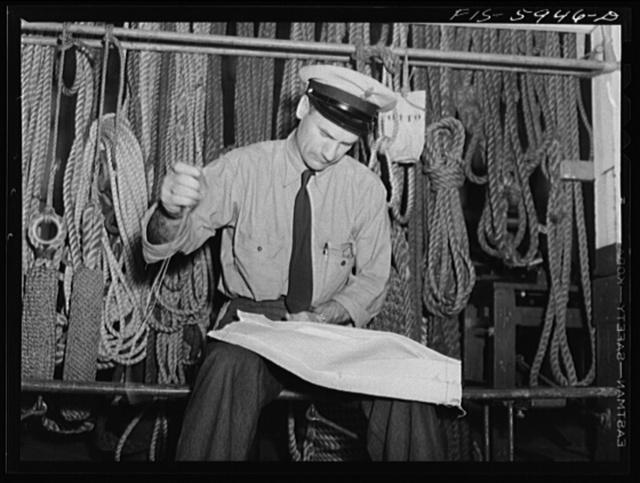 Hoffman Island, merchant marine training center off Staten Island, New York. An instructor sewing a piece of canvas