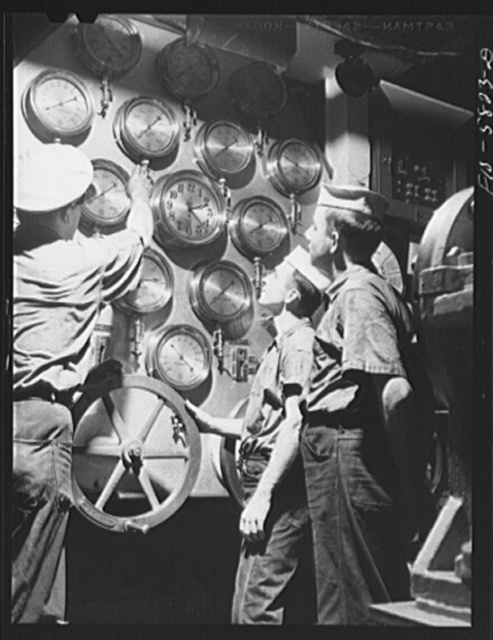 Hoffman Island, merchant marine training center off Staten Island, New York. Instructor with trainees as the main control board in the engine room of the training ship New York