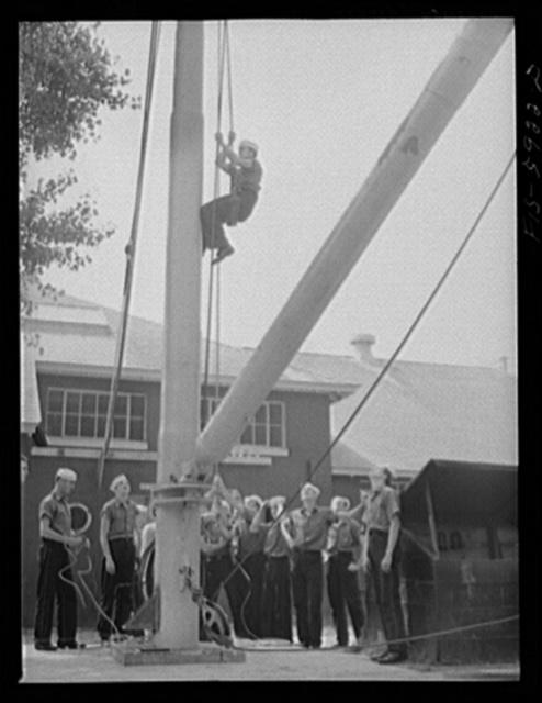 Hoffman Island, merchant marine training center off Staten Island, New York. Trainee going up the boom in a bosun's chair