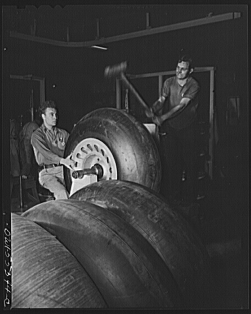 Huge rubber tires for North American B-25 bombers are mounted ready for assembly. The mallet is used in the balancing operation