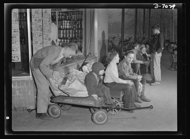 I'll carry mine. Delivery vans, 1942 style, line up outside a Greenbelt, Maryland, grocery store awaiting customers. Tire scarcity and gasoline rationing have placed such service at a premium, and these youngsters who are using their express wagons to carry home Mrs. America's purchases are doing their country a real service