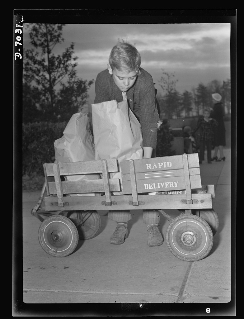 I'll carry mine. Junior's express wagon comes of age and assumes new importance in wartime America's shopping expeditions. To conserve transportation facilities and thus save rubber and gasoline, shippers must devise their own methods of getting their purchases home. This one is among the best!