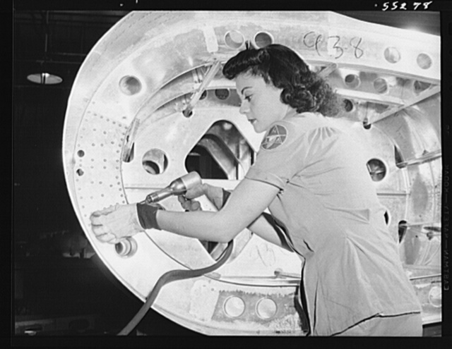 In North American's tank department, a woman employee rivets a rib. Tanks like these with high test gasoline enable United Nations bombers to fly faster and farther