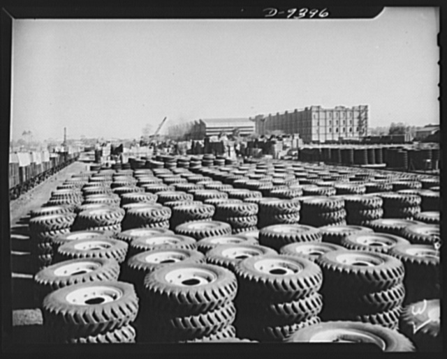 Indian rubber. Tires for the machines of war are part of the great stock pile of equipment at an Indian port city. Much of this material has been shipped to India by lend-lease. Barrage balloons protect the stockpile