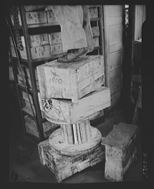 """Industrial safety. Accident prevention. This shop worker is """"asking for it."""" The use of a makeshift """"ladder"""" like this is always hazardous--doubly so when heavy, bulky, or unwieldy objects are being put in place or removed"""