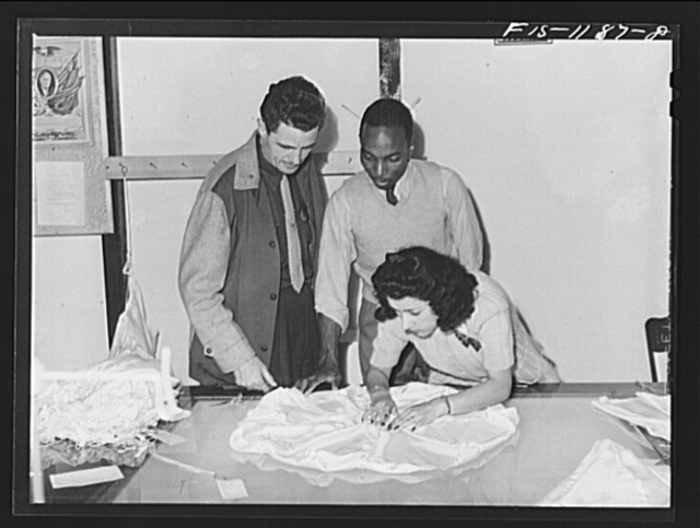 """Inspector of the Standard Parachute Company and """"Skippy"""" Smith, manager of the Pacific Parachute Company (subcontractors of Standard Parachute), watch final inspection of pilot parachutes being made at the Pacific Parachute Company. San Diego, California"""