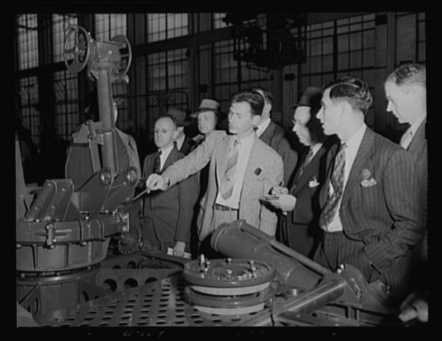 Inspectors instructed. Student inspectors learn the ins and outs of their trade at an eastern arsenal. The mechanism under discussion is that of a 37 mm gun anti-aircraft carriage, M-3, one of the army being turned out for war work