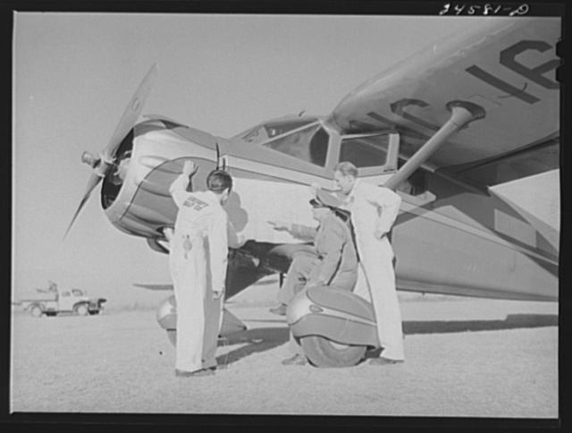 Instructor and students studying map. Civilian pilot training school. Meacham Field, Fort Worth, Texas