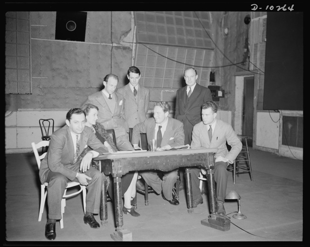 """Jack Schaindlin, musical director, Eleanor Herring, Garson Kanin, director, Wallace Russell, writer, Spencer Tracy, narrator, Max Brasch, film editor, Philip Martin, Jr., technical director, at the Long Island Studios of the Army Signal Corps for the recording of Spencer Tracy's narration of the """"Ring of Steel,"""" an Office of Emergency Management (OEM) film, on February 19, 1942"""