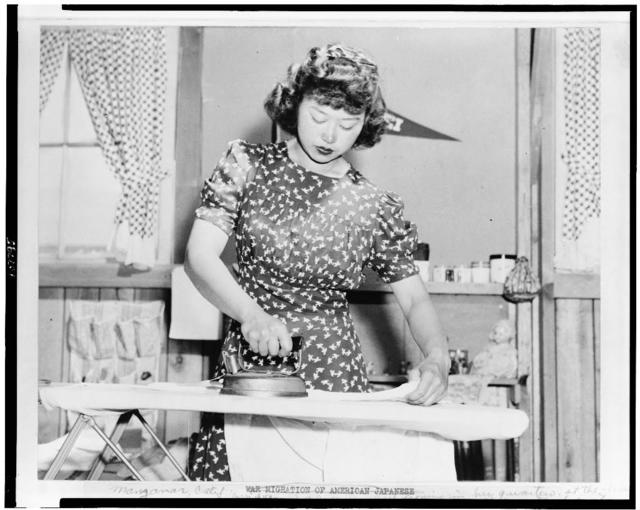 Japanese relocation, California. Ester Naite, an office worker from Los Angeles, is shown operating an electric iron in her quarters at Manzanar, California, a War Relocation Authority center where evacuees of Japanese ancestry will spend the duration. Miss Naito works in an office at the center