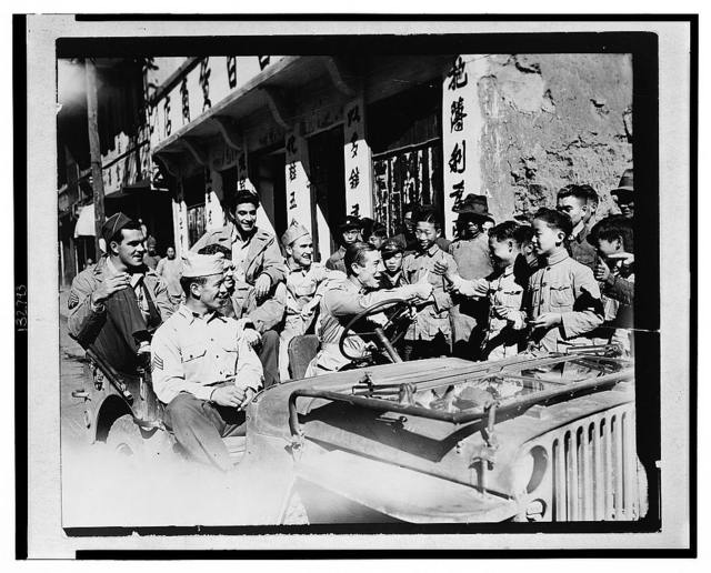 Joe E. Brown driving jeep loaded with American G.I.'s seeing the sights of China