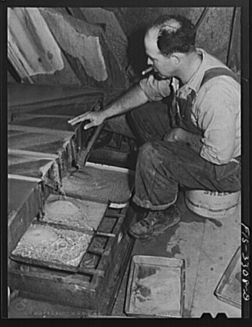 Kern County, California. Mill of the Tungsten Chief Mine. Pulverized tungsten ore is mixed with water and then run over a vibratory table where the ore is further concentrated; in this picture the final concentrates appear in the two pans in the lower left hand corner