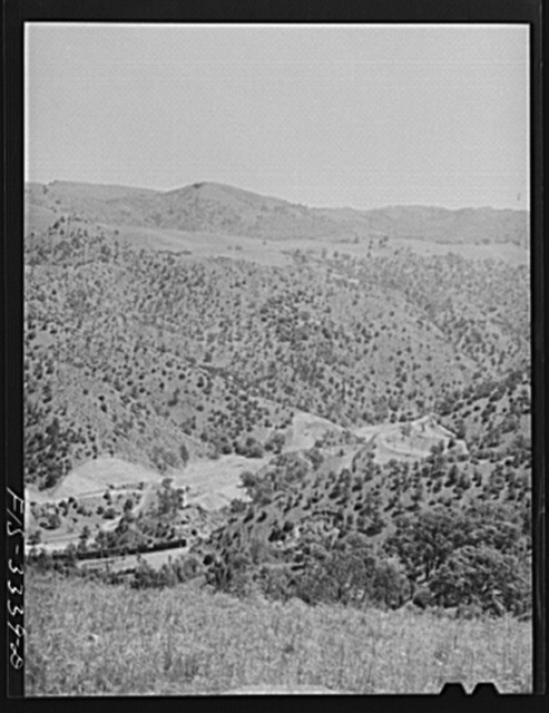 Kern County, California. Train going through a valley in the mountains